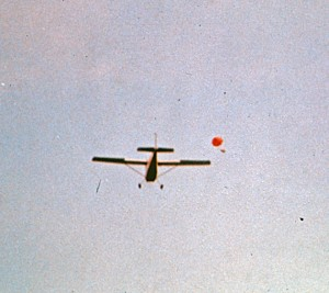 A early project in which polystyrene boxes with bees were air-dropped into cranberry bogs for pollination services. The red spot is a parachute with the small hive attached. The unit was queenless. Ultimately, the idea did not work efficiently.